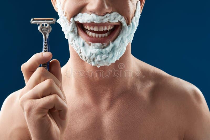 Geerntetes Foto des jungen Kerls sein Rasiermesser zeigend stockfoto