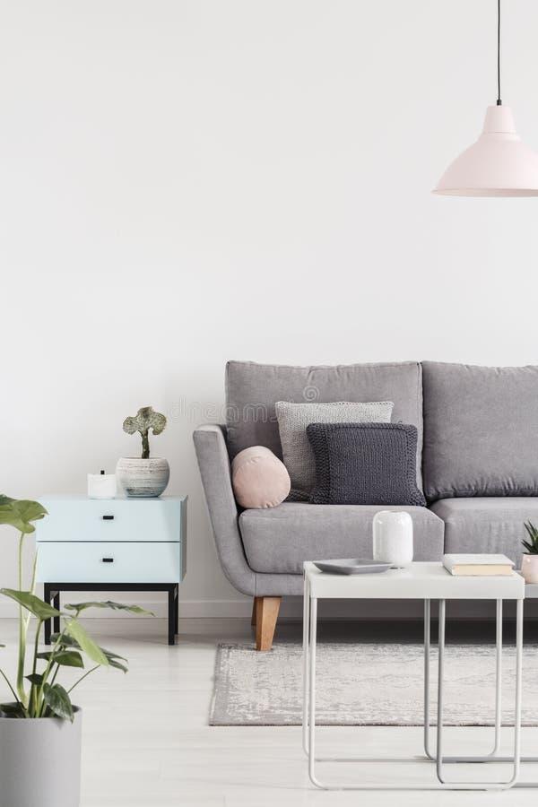 Geerntetes Foto eines Sofas nahe bei kleiner Kabinett- und Kaffeetabelle i lizenzfreie stockfotos