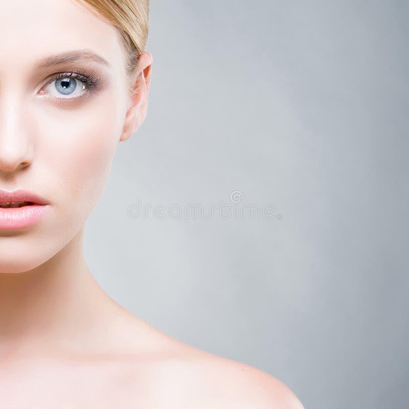 Geerntetes Gesicht einer Schönheit mit blauen Augen Nahaufnahmeportrait getrennt auf Weiß stockfotografie