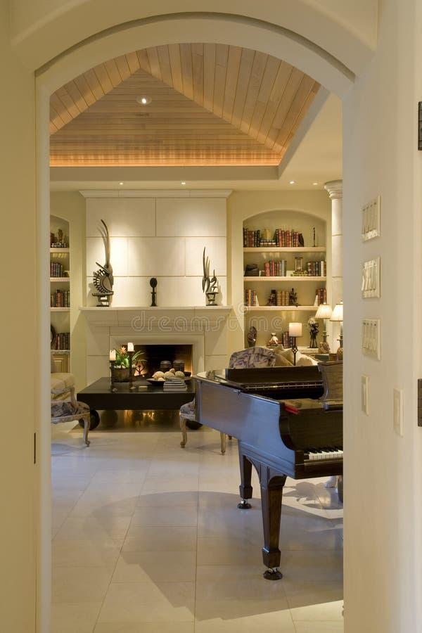 Geerntetes Klavier gegen Fach und Kamin im Wohnzimmer stockfoto