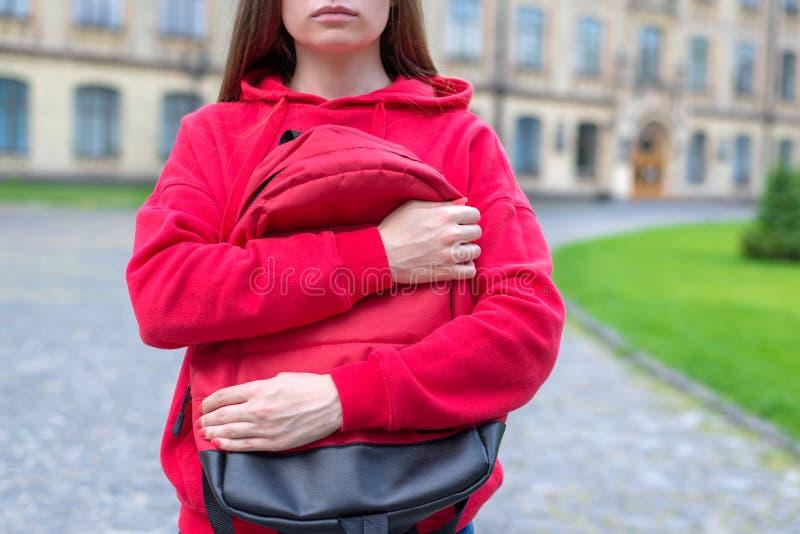 Geerntetes Nahaufnahmefoto von ernstem ohne Lächeln auf dem Gesichtsknaben, der ihre Taschenstellung nahe Gebäudeeingang umarmt stockfoto