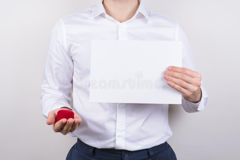 Geerntetes Nahaufnahmefotoporträt des glücklichen aufgeregten netten Kerls, der weißes Anschlagtafelplakat in den Händen zeigen c stockfotos
