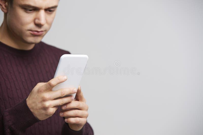 Geerntetes Porträt eines jungen weißen Mannes, der einen Smartphone verwendet lizenzfreie stockfotografie