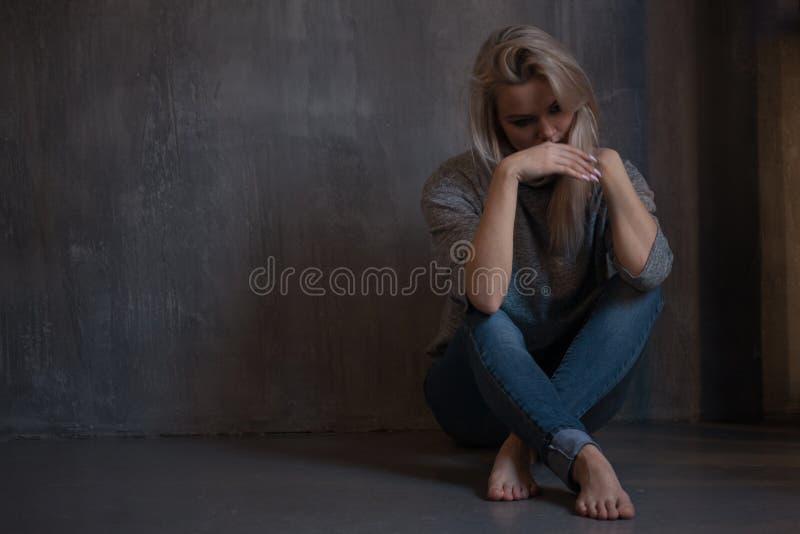 Geestelijke Gezondheid Jonge vrouwenzitting op de vloer stock afbeeldingen
