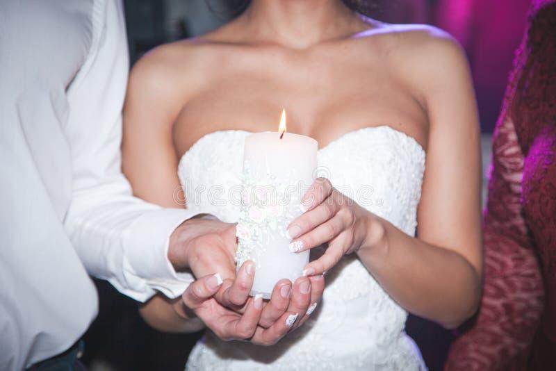 Geestelijke paar, bruid en bruidegomholdingskaarsen tijdens huwelijksceremonie in christelijke kerk, emotioneel ogenblik tijdens stock foto