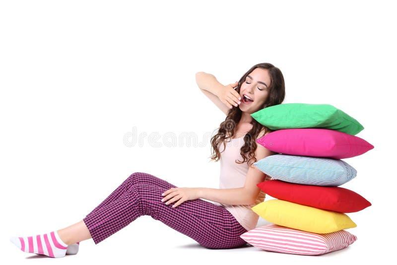 Geeuwend meisje met kleurrijke hoofdkussens stock afbeeldingen