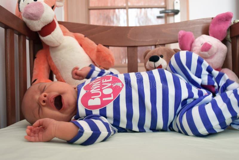Geeuwende baby in voederbak stock afbeeldingen