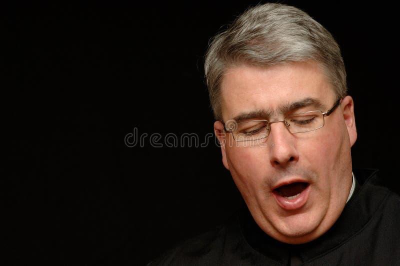 Geeuwende priester royalty-vrije stock afbeelding