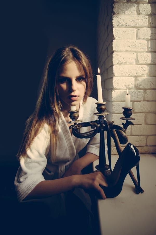 Gefährlich schön Frau mit Schuh und Kerzenständer des hohen Absatzes mit Schlange Junge Frau mit langer Haargriffmode lizenzfreies stockfoto