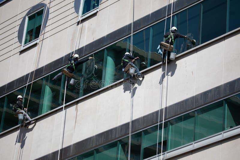 Gefährliche Besetzungs-blauer Kragen-baumelnde Seil-Fensterputzer verschoben errichtendes Äußeres stockfoto