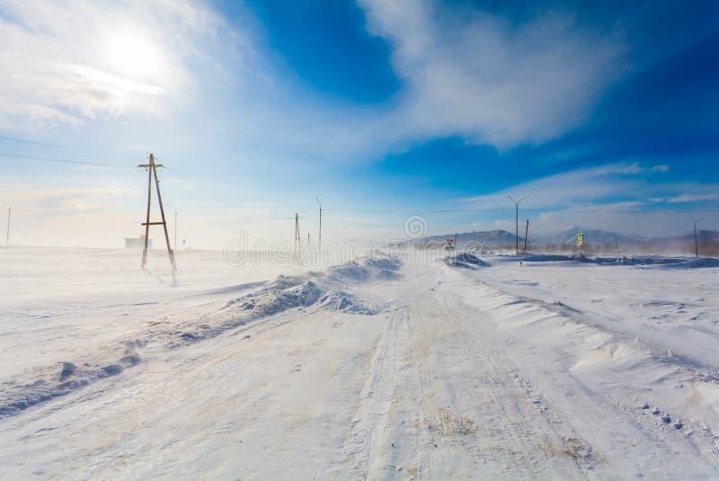 Gefährliche schneiende Straße mit Verkehrsschildern für das Fahren von Autos und von öffentlichen Transportmitteln während des Bl lizenzfreie stockfotografie