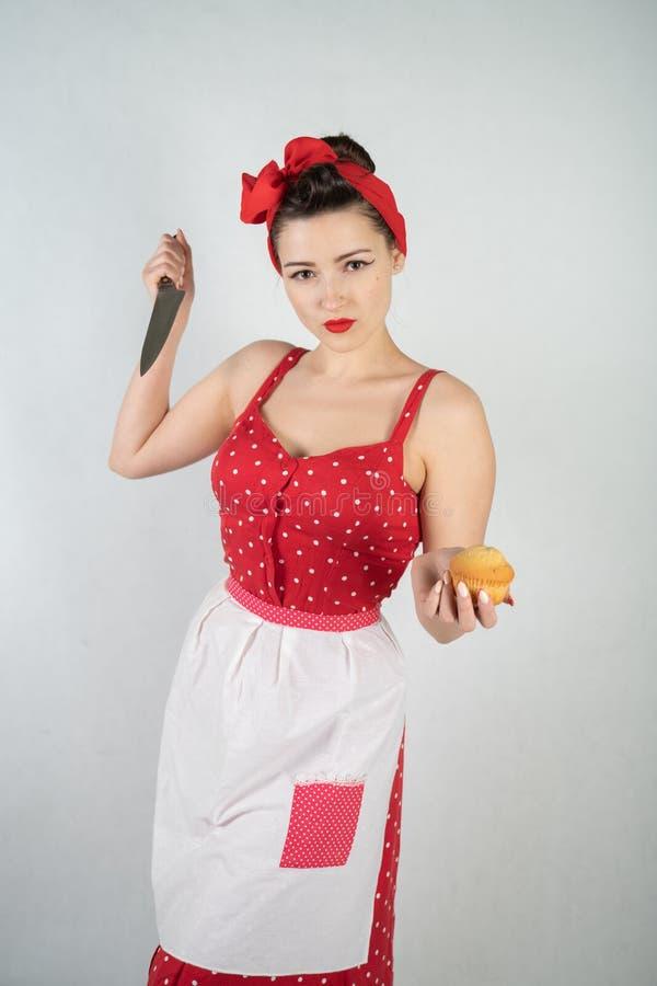 Gefährlicher Stift herauf Mädchenhausfrau im roten Weinlesetupfenkleid steht mit einem Messer der großen Küche in ihren Händen un lizenzfreies stockbild