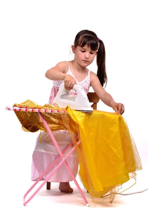 Gefährliches Hausarbeit-kleines Mädchen, das ihr Kleid bügelt lizenzfreie stockbilder
