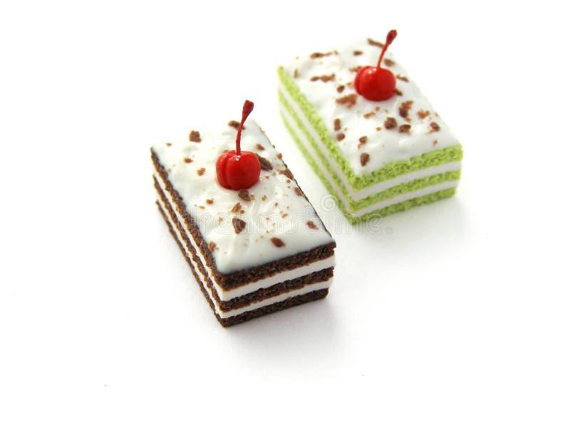 Gefälschte rechteckige Miniaturkuchen des Fotos mit Schlagsahne und Kirsche lizenzfreies stockfoto