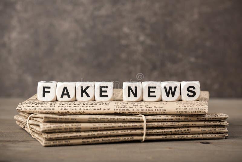 Gefälschtes Nachrichtenkonzept mit Zeitungen und Würfeln mit Buchstaben lizenzfreie stockfotografie