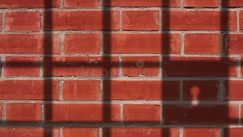 Gefängnis-Schatten auf Wand der roten Backsteine stockfoto