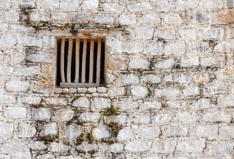 Gefängniszellenfenster mit hölzernen Stangen in einer weißen Backsteinmauer lizenzfreie stockfotografie