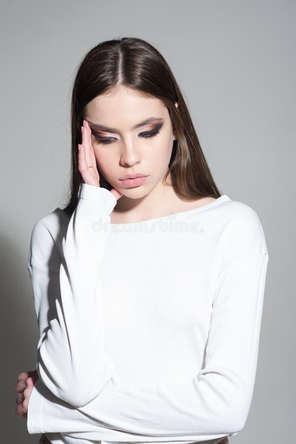 Gefühl betont Modische Frau mit dem stilvollen Haar und modernem Make-up Müdes Mädchen auf grauem Hintergrund Make-up smokey stockfotos