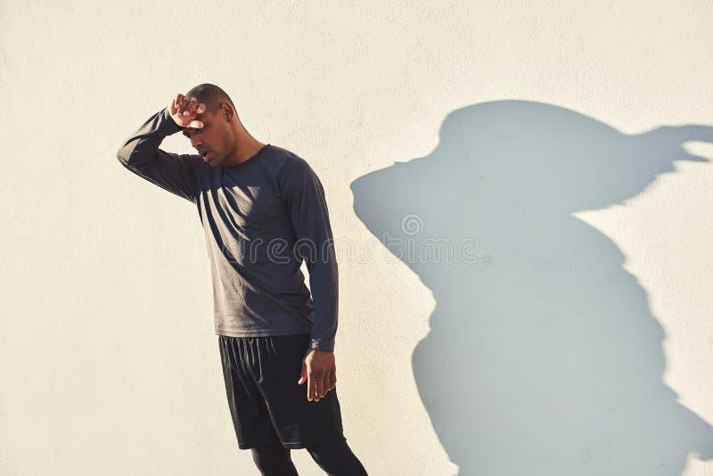 Gefühl erschöpft Müder afrikanischer Athlet in der Sportkleidung, welche die Stirn, stehend nach Training im Freien bei der Stell stockfotos