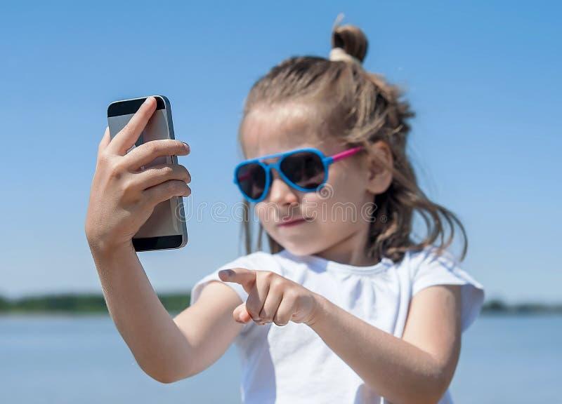 Gefühle, Ausdrücke und Leutekonzept - glückliches Kleinkind oder Jugendliche, die selfie mit Smartphone über blauem Himmel und Wo stockbild