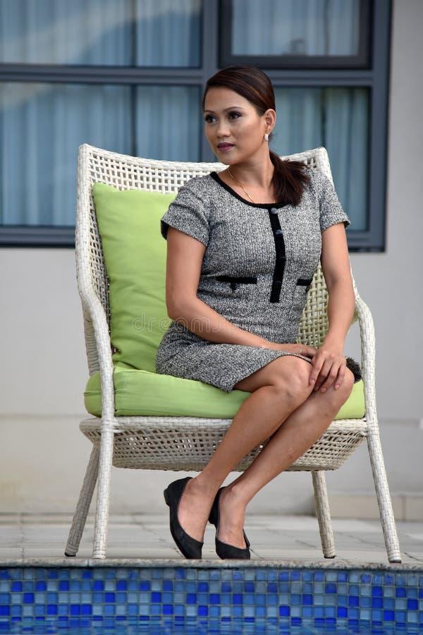 Gefühllose jugendliche asiatische Frau, die durch Eigentumswohnung sitzt lizenzfreie stockfotografie