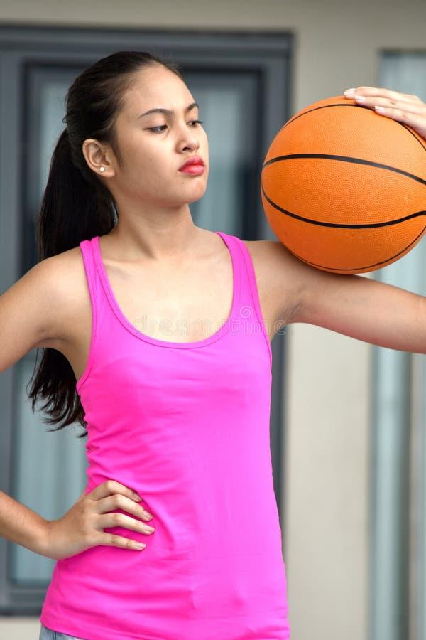 Gefühlloser Sitz-asiatischer jugendlich Athlet Female Basketball Player stockfotos