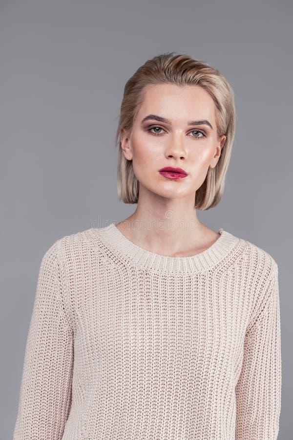 Gefühlloses blondes junges Mädchen, das beige gestrickte Strickjacke trägt lizenzfreie stockbilder