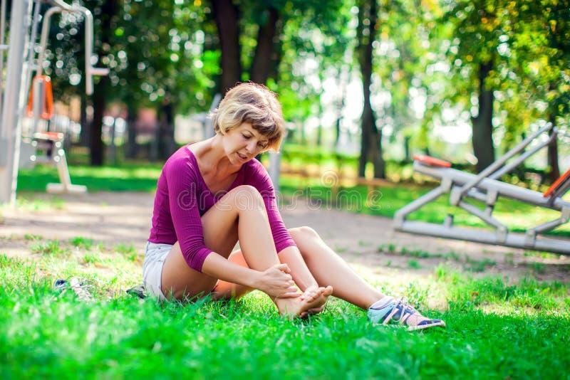 Gefühlsschmerz der jungen Frau in ihrem Fuß während des Sporttrainings in lizenzfreie stockfotografie