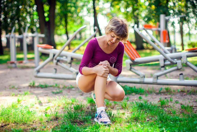 Gefühlsschmerz der jungen Frau in ihrem Knie während des Sporttrainings in lizenzfreie stockbilder
