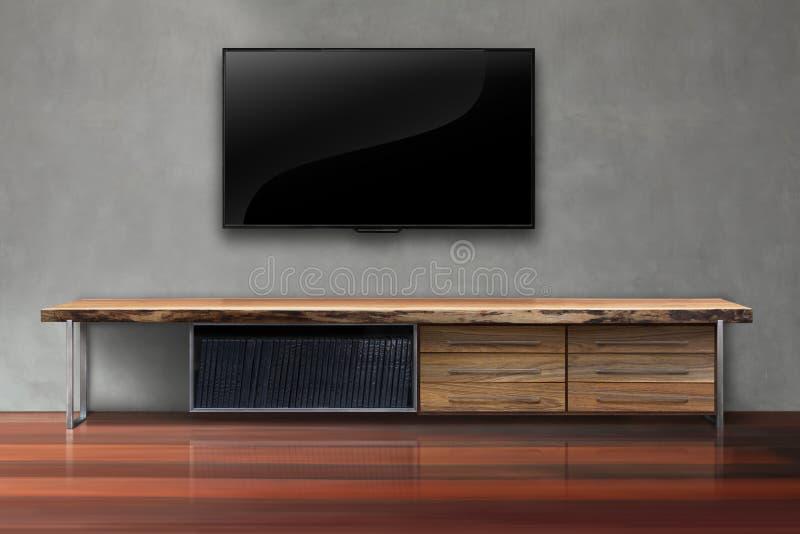 Geführtes Fernsehen auf Betonmauer mit Holztischwohnzimmer stockfotografie