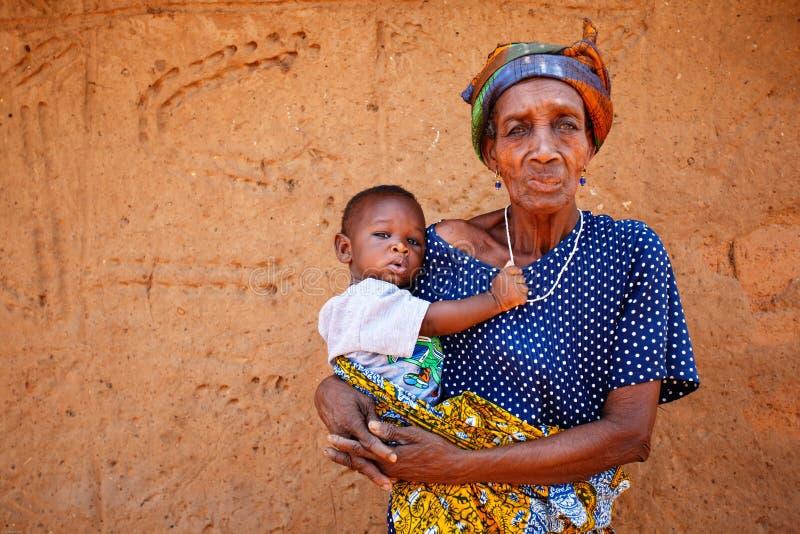 GEFÜLLTE MAISMEHLTASCHE, GHANA-ï ¿ ½ am 24. März: Nicht identifizierte alte Afrikanerinholding lizenzfreie stockfotografie