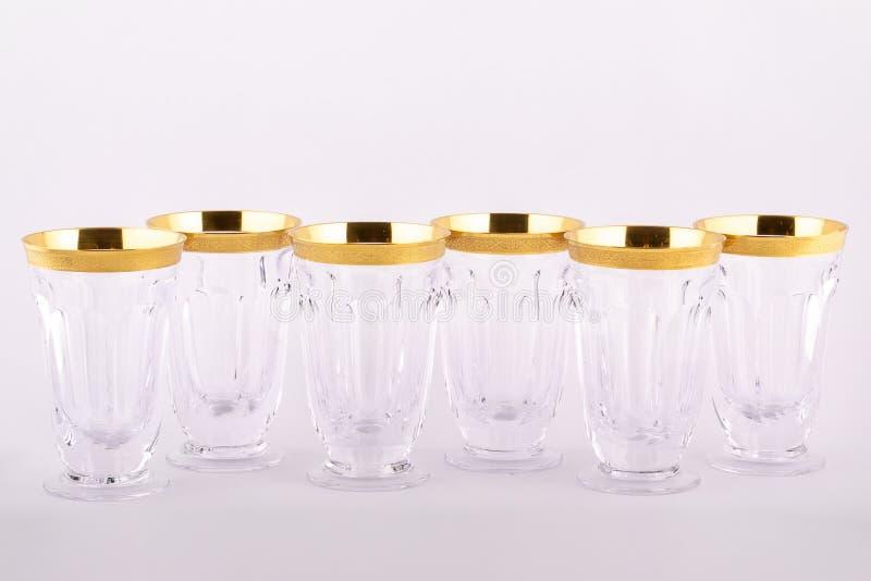 Gefacetteerde die kopglazen van Tsjechisch glas met tot Gouden die lijnen worden gemaakt en ornament op een witte achtergrond wor stock afbeeldingen