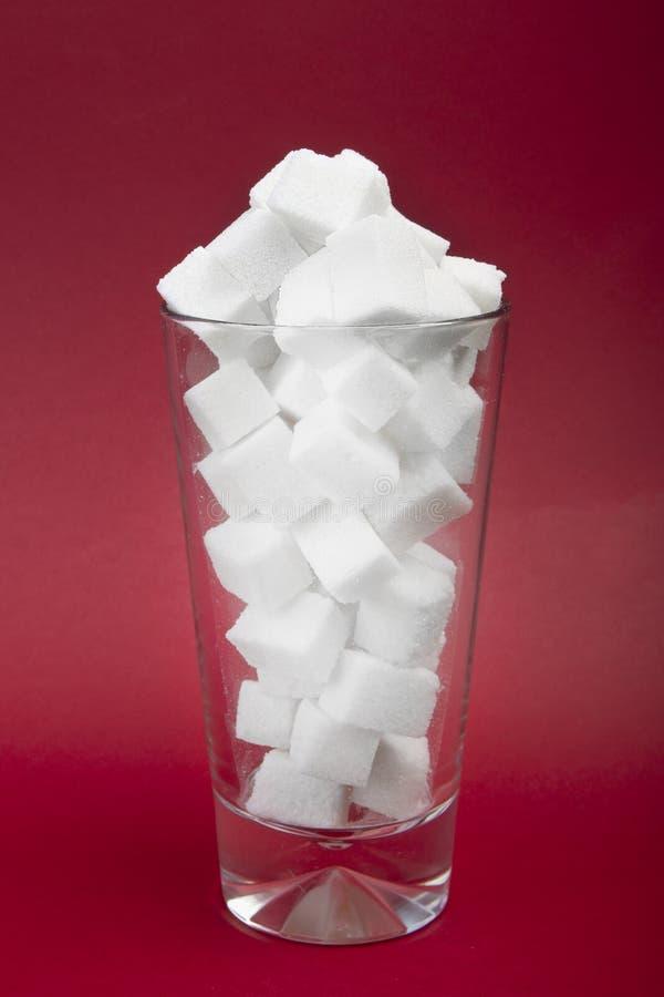 Gefahr des Zuckers in gekohlten Getränken Konzept von Korpulenz Würfel des raffinierten Zuckers auf dem Glas auf rotem Hintergrun lizenzfreies stockbild