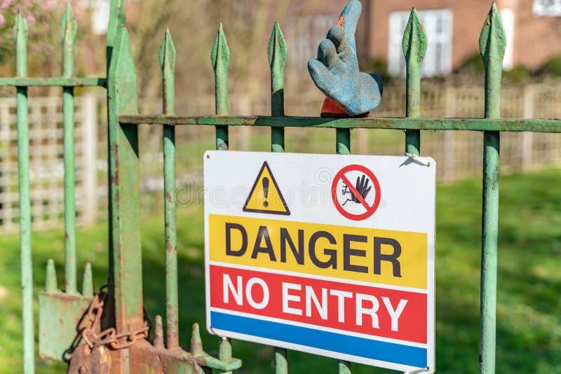 Gefahr kein Eingangszeichen und grüner Gummihandschuh auf Gartentor stockfotografie