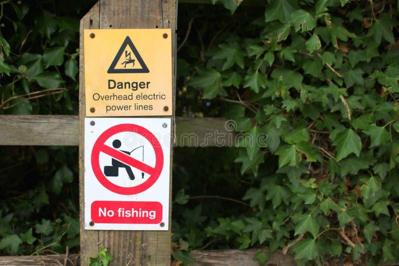 Gefahr kein Fischen und Stromleitung Zeichen lizenzfreies stockbild