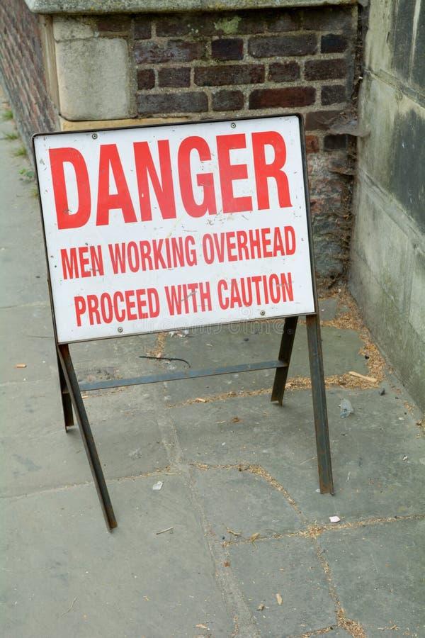 Gefahr - Männer, die oben arbeiten - fahren Sie mit Vorsichtzeichen fort stockbild