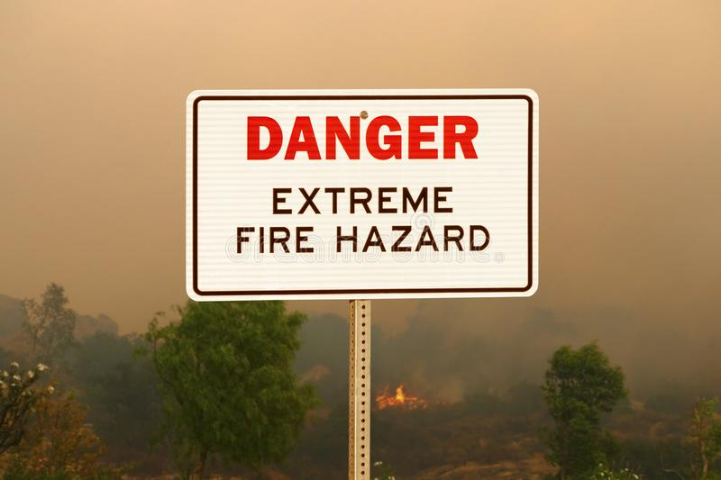 Gefahrenextremes Feuer HazardSign mit Hintergrund des verheerenden Feuers stockfotografie