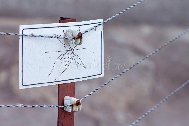 Gefahrenhochspannungswarnzeichen auf einem elektrifizierten Zaun stockfotografie