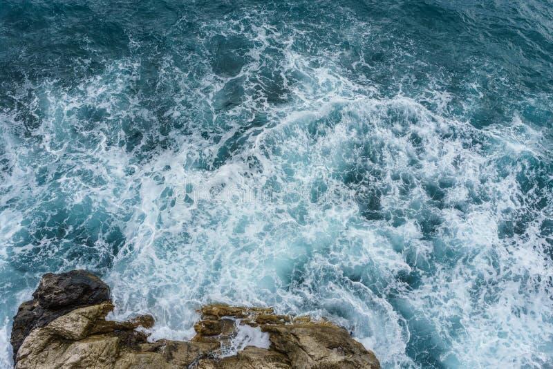 Gefahrenseemeereswoge, der auf Felsenküste mit Spray und Schaum zusammenstößt lizenzfreies stockbild