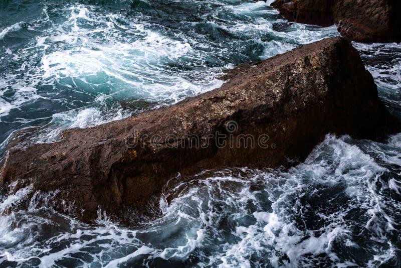 Gefahrenseewelle, die auf Felsen zusammenstößt stockfotos