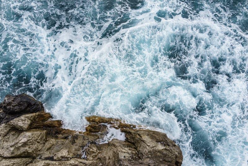 Gefahrenseewelle, die auf Felsenküste mit Spray zusammenstoßen und Schaum windig stockfotografie