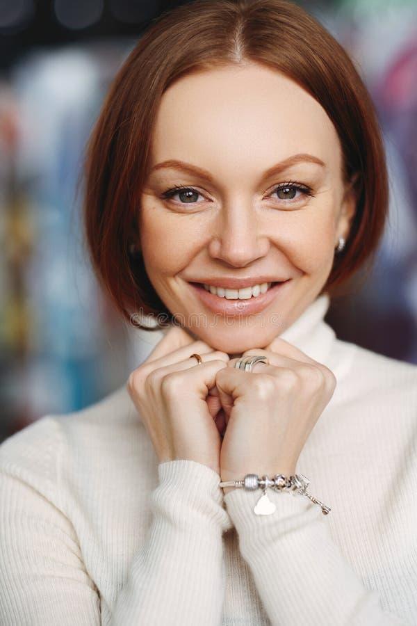 Gefallene reizende Frau mit bilden, halten Hände unter Kinn, hat braunes Haar, betrachtet glücklich der Kamera, gekleidet in der  lizenzfreie stockfotografie