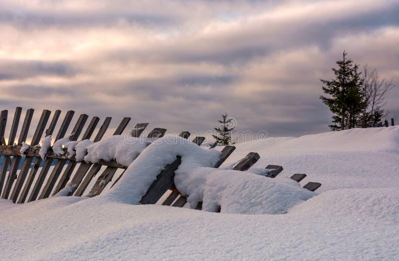 Gefallener Bretterzaun auf schneebedecktem Abhang stockbild