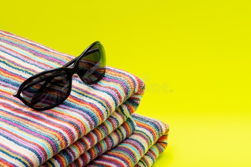 Gefaltete bunte gestreifte Biobaumwolle-Badetücher und schwarze Sonnenbrille auf hellem Gelb als Sommer-Ferien-Thema stockfoto