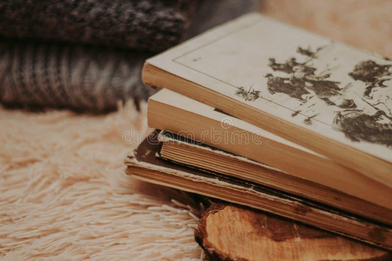 Gefaltete gestrickte woolen Strickjacken, Stapel alte Bücher auf einer gemütlichen flaumigen beige Decke lizenzfreie stockfotografie
