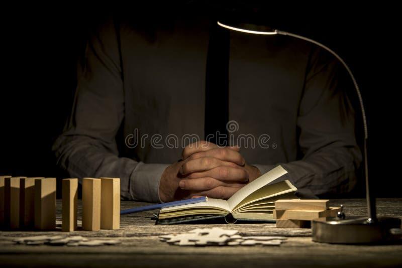 Gefaltete Hände nähern sich Buch- und Puzzlespielstücken lizenzfreies stockbild