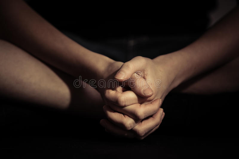 Gefaltete Hände in Sitzposition lizenzfreie stockfotos