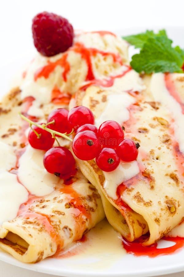 Gefaltete Pfannkuchen mit Vanille- und Himbeeresoße lizenzfreies stockbild