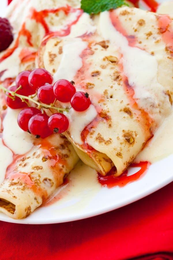 Gefaltete Pfannkuchen mit Vanille- und Himbeeresoße lizenzfreie stockfotos