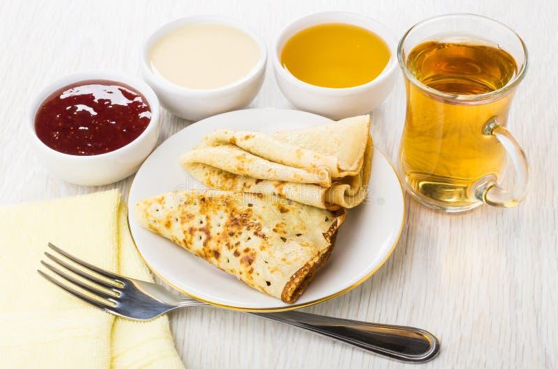 Gefaltete Pfannkuchen, Stau, Honig, Kondensmilch, Gabel, Tasse Tee lizenzfreie stockfotos